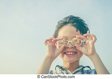 Young boy holding shell over sky background