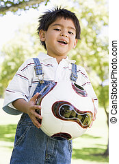 Young boy holding soccer ball outdoors smiling