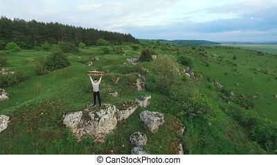 Young boy holds homemade airplane on the rock. Aerial view