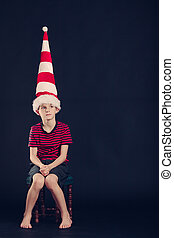 Young boy in a red and white striped dunce cap