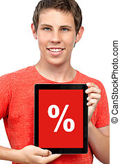 young boy in a t-shirt holding a tablet touch computer gadget with a discount percent on a red screen