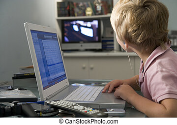 Young boy in bedroom using laptop and listening to MP3 ...