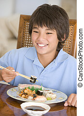 Young boy in dining room eating chinese food smiling