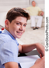 Young boy in focus, studying and smiling at camera
