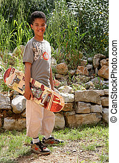 Young boy in garden with skateboard