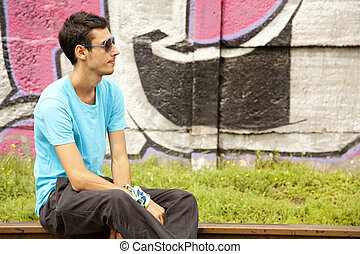 Young boy in glasses sitting at railway