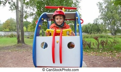 young boy in helmet swings in toy helicopter in children playground