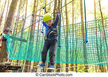 Young boy in helmet walks by rope