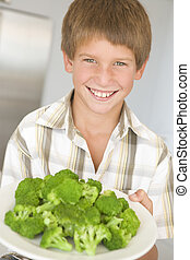 Young boy in kitchen eating broccoli smiling