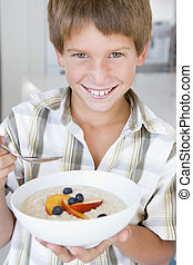 Young boy in kitchen eating oatmeal with fruit smiling
