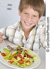 Young boy in kitchen eating salad smiling