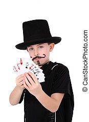 Young boy in magician costume with cards