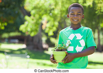 Young boy in recycling tshirt holding potted plant on a...