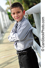 Young boy in suit with arms crossed
