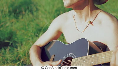 Young boy in sunglasses and hat playing the guitar on the nature. 4k