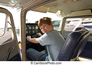 young boy in the pilot seat at the airport