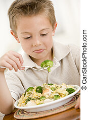 Young boy indoors eating pasta with brocolli