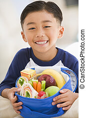 Young boy indoors with packed lunch smiling