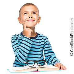 Young boy is daydreaming while reading book, isolated over...