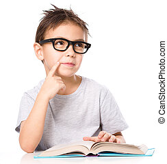 Young boy is daydreaming while reading book and wearing...