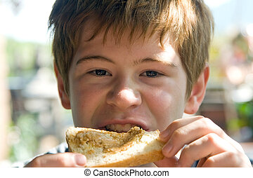 young boy is eating toast with cream on top, enjoying meal
