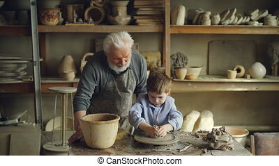 Young boy is making clay sculpture on potter's wheel while...