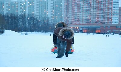 Young boy is pulling sled hardly with other boy in winter
