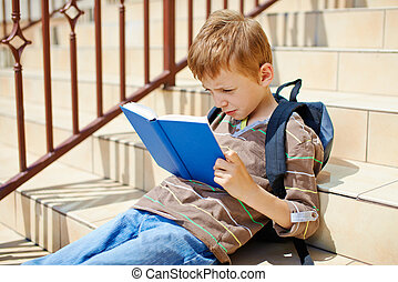 Young boy is reading book