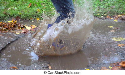 young boy jumping in muddy puddle, slow motion