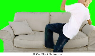 Young boy jumping on the sofa on gr