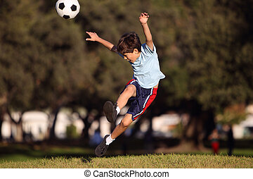 Young boy kicking a soccer ball in the park