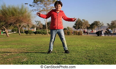 Young boy kicking ball in the grass
