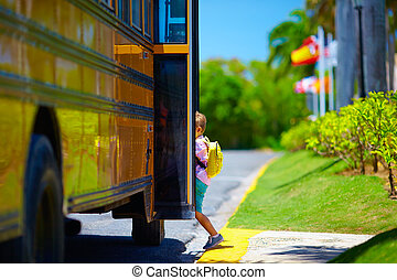 young boy, kid getting on the schoolbus, ready to go to school
