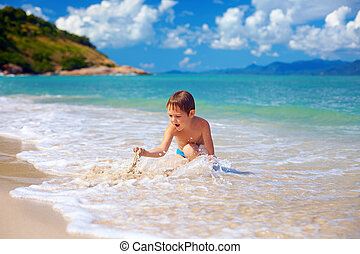 young boy, kid playing with sand in surf
