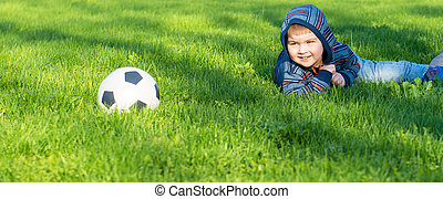 Young boy laying on an green grass