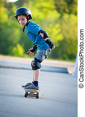 young boy learning how to skateboard