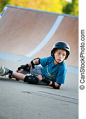 young boy learning to skateboard falls over