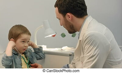 Young boy listening to doctor's heart with stethoscope....