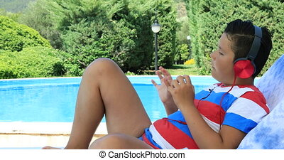 Young boy listening to music near the pool - Portrait of...
