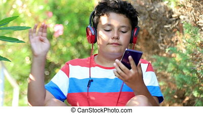 Young boy listeninng to music at the nature - Portrait of...