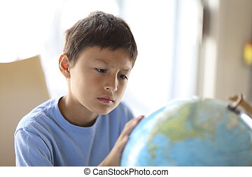 Young boy looking at a globe