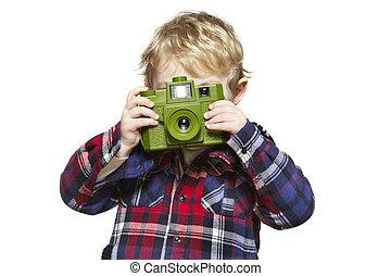 Young boy looking through a camera
