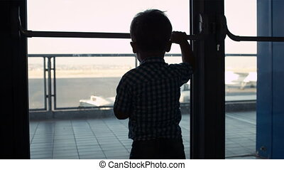 Young boy looking through window in the airport