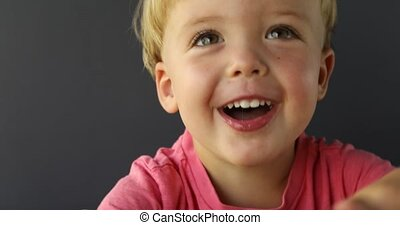 Young boy looks at the camera and smiling