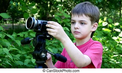 Young boy looks into video camera on background of green park.