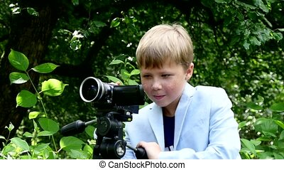 Young boy looks into video shoots movie about nature on green park slow motion.