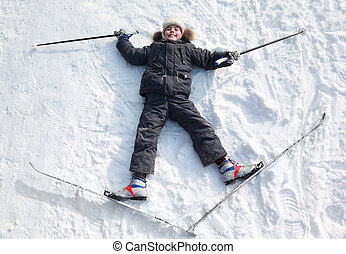 Young boy lying in cross-country skis and poles and...