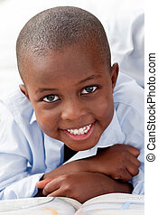 Young boy lying on his bed smiling - Young boy lying on his...