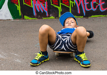 Young Boy Lying on Skateboard in Paved Lot