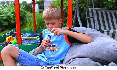Young boy making bubbles in the park
